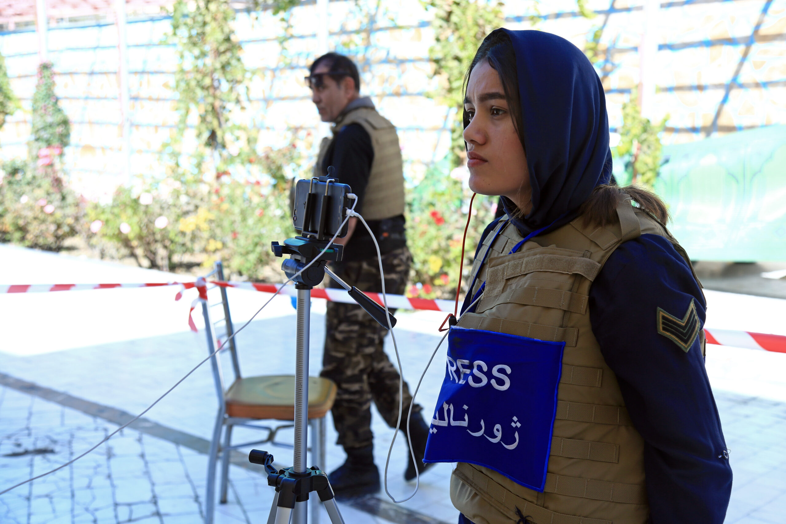 woman wearing a flak jacket with Press written on the torso in English and Arabic