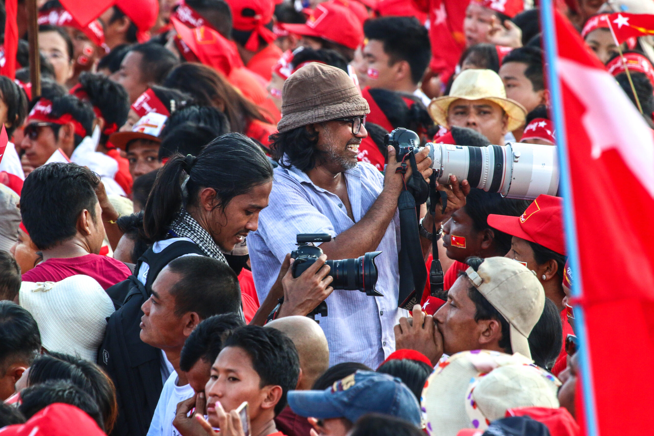 Photographers ina crowd of red flags during the 2015 Myanmar elections