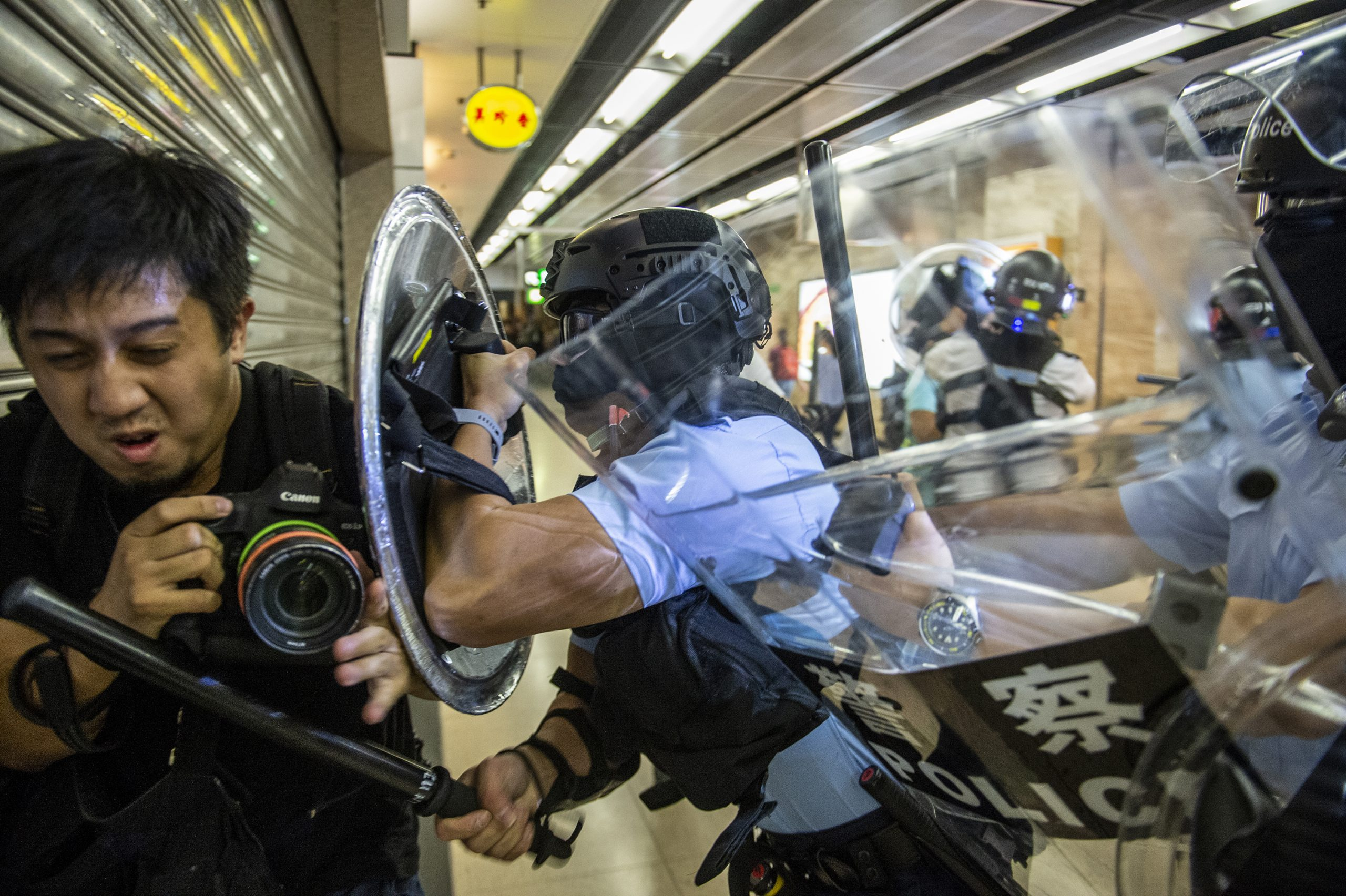 A photographer is attacked by police during an anti-government protest.